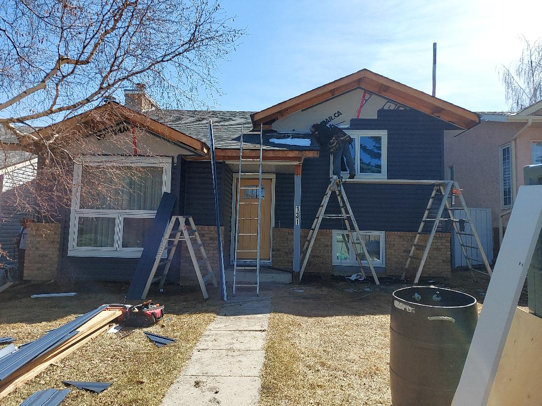 """Calgary, AB - SW Calgary exterior refresh, removed the old wood siding, installed new Royal Estate Marine Blue siding with Arctic White Hardie Trim Accents. Beautiful new Portatec front door factory painted in Sherwin Williams """"Anjou Pear."""""""