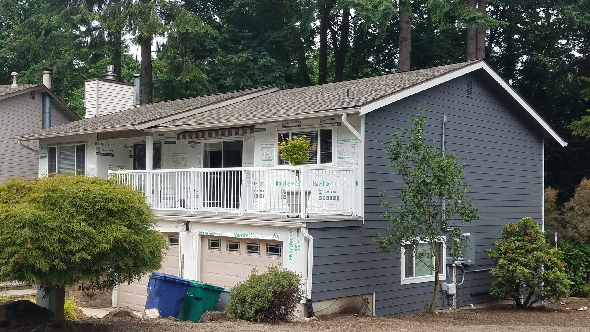 Kirkland, WA - Another siding replacement with Hardieplank Color Plus in Evening Blue.  Arctic White Hardir Trim.  Also Hardie Soffit and fascia,  new gutters, and new decking.