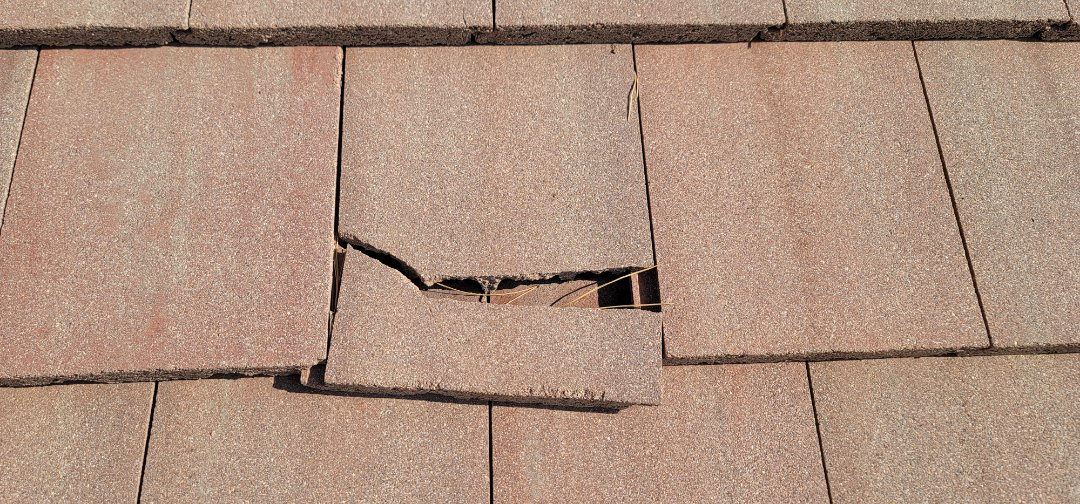 Aurora, CO - We are doing a roof inspection for this concrete tile roof in Aurora that has a tile that came off the roof due to tree branches knocking it off in the wind. There are also many other broken roof tiles that need to be replaced