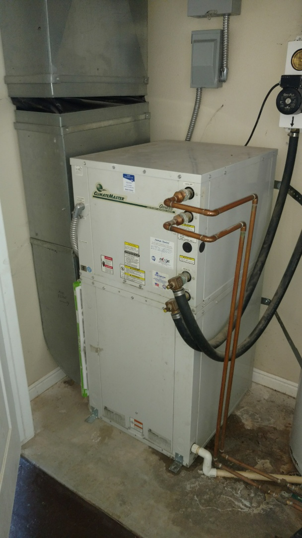 Ivins, UT - Dixie Heating and Air Conditioning clearing plug in condensate drain that tripped drain overflow switch on Climate Master geothermal heat pump