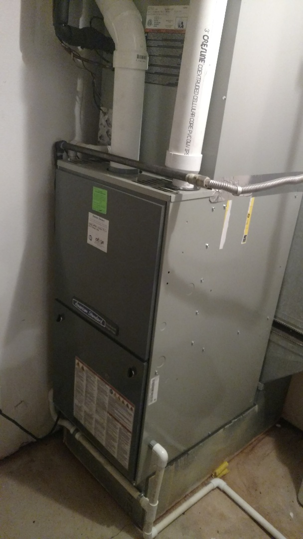 Hurricane, UT - Dixie Heating and Air Conditioning performing routine maintenance on American Standard furnace and clearing plug in condensing furnace drain