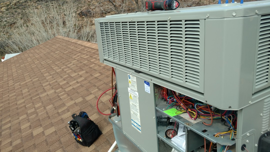 Hurricane, UT - Dixie Heating and Air Conditioning performing routine maintenance on American Standard package gas electric AC unit