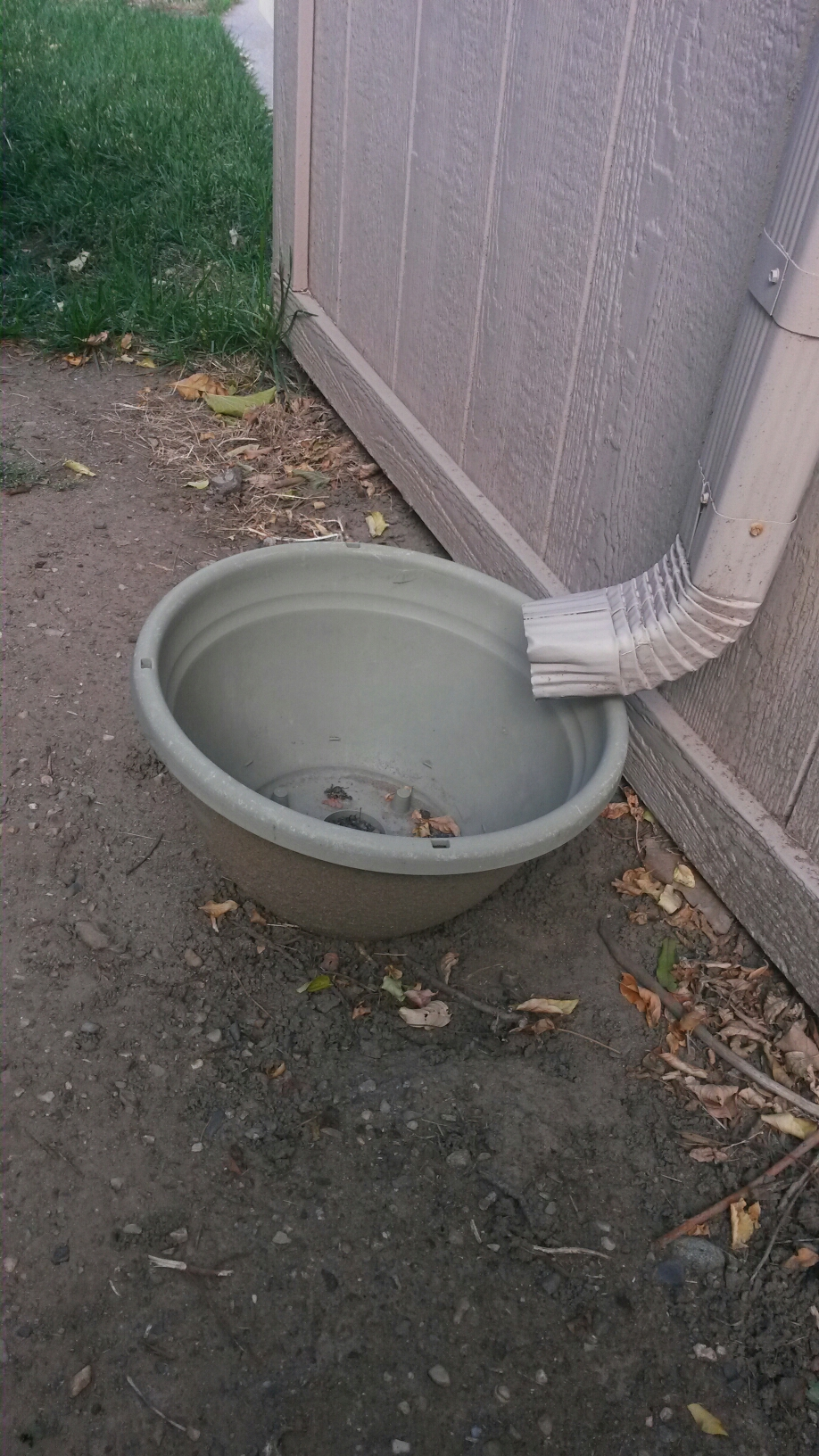 Cottonwood Heights, UT - There are a lot of systems that make up our homes. When they work everything is good. When they don't work it can lead to problems. The picture shows a system that is not good. It's a downspout from a rain gutter that empties into a bucket, and a negative slope towards the house. This is not a good system, it could lead to water damage and possible mold.