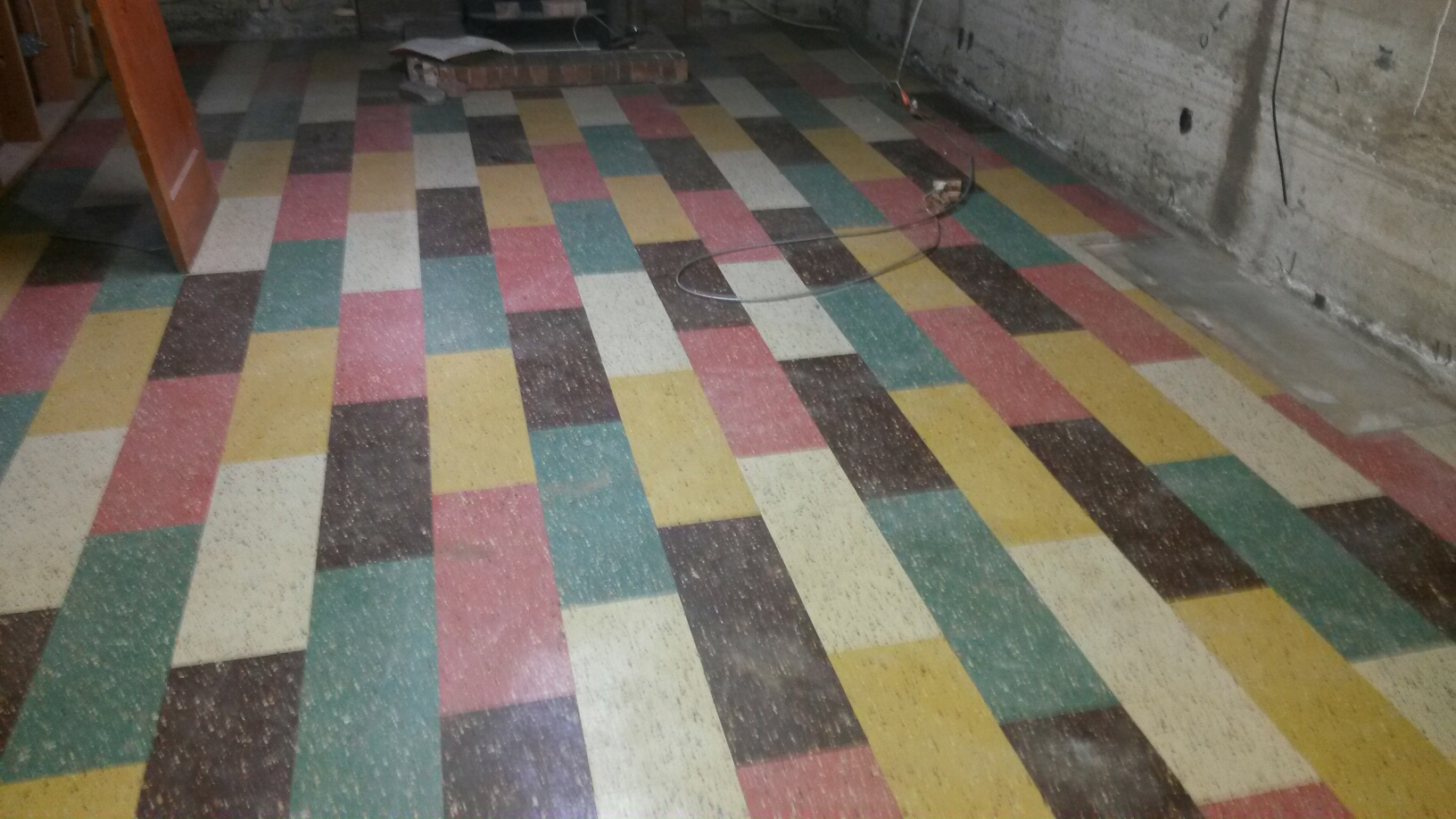 Ogden, UT - Sewage backed up and water damage cleanup in Ogden Utah. After we took out the carpet and padding we uncovered this fun VCT tile from the 1950s. It's very colorful still in pretty good shape and would have been very much in style in its day I'm sure. It is in good enough shape we were able to clean and disinfect the floor but there's other tile in the bathroom that the tiles will need to come up because some of the tiles are coming up on their own already.