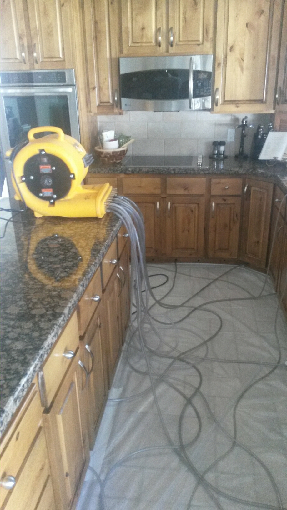 Taylorsville, UT - Water damage Cleanup in Taylorsville Utah. This is a beautiful home with a beautiful kitchen. We are trying to dry everything out to minimize the repairs. We are blowing warm air under the cabinets to dry under them.
