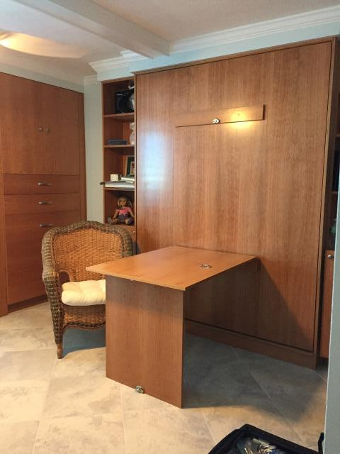 clear coated Cherry wood Murphy Bed with fold out table.  A home office by day and a guest room by night.  Attached book shelves with drawers and a cabinet house a file drawers, and hanging.