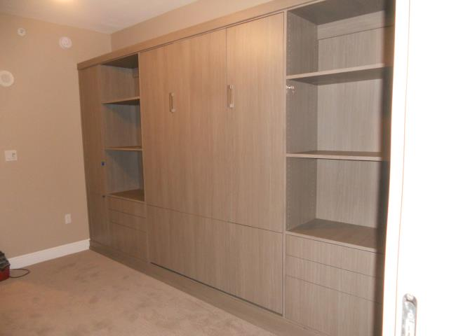 Murphy Bed installed with added storage for Ironing board on far left, hanging with drawers for guests, and shelves with file cabinets for multiple use of the room