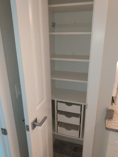 Fabrication and Installation of a Linen Closet., done in White Melamine with Scoop Front Drawers.