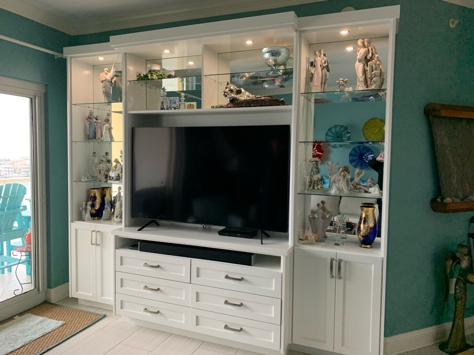 Custom entertainment center with mirrored back, designed to fit Tv in an appropriate scale, adjustable glass shelves , soundbar cubbie, drawers and cabinets euro crown to finish.  Painted to match decor