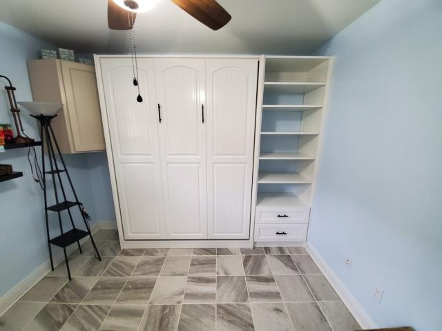 Milton, FL - Design, Fabrication and Installation of a Queen Murphy Bed with a Side Cabinet creating extra storage for the room. Created in Maple and finished in our custom Alpha White with V Groove Arch Door and Drawer Fronts made from MDF and finished in our Custom Alpha White.