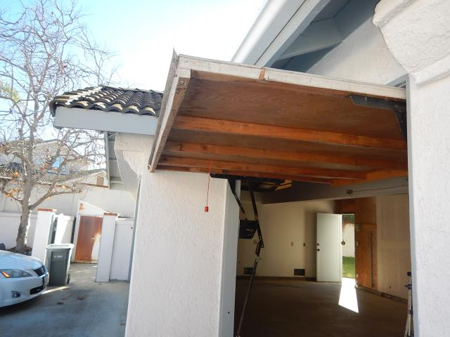 Older wood tilt up door was found to be damaged. This type of garage door is highly recommended for replacement to a newer modern garage door.