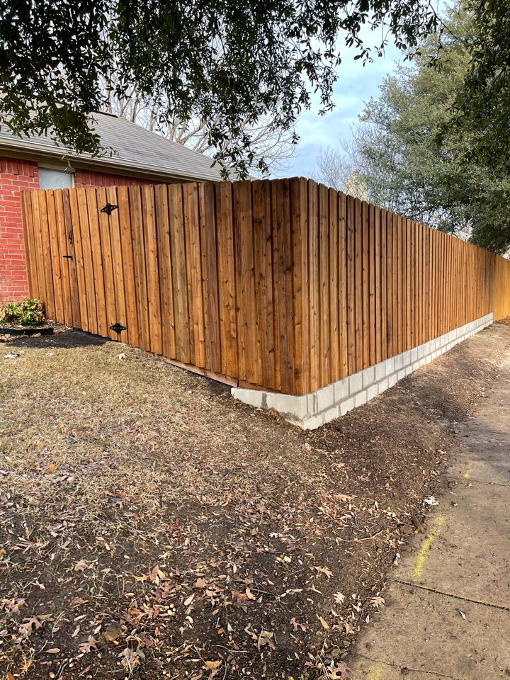 Install me stained cedar board on board fence with small retaining wall.