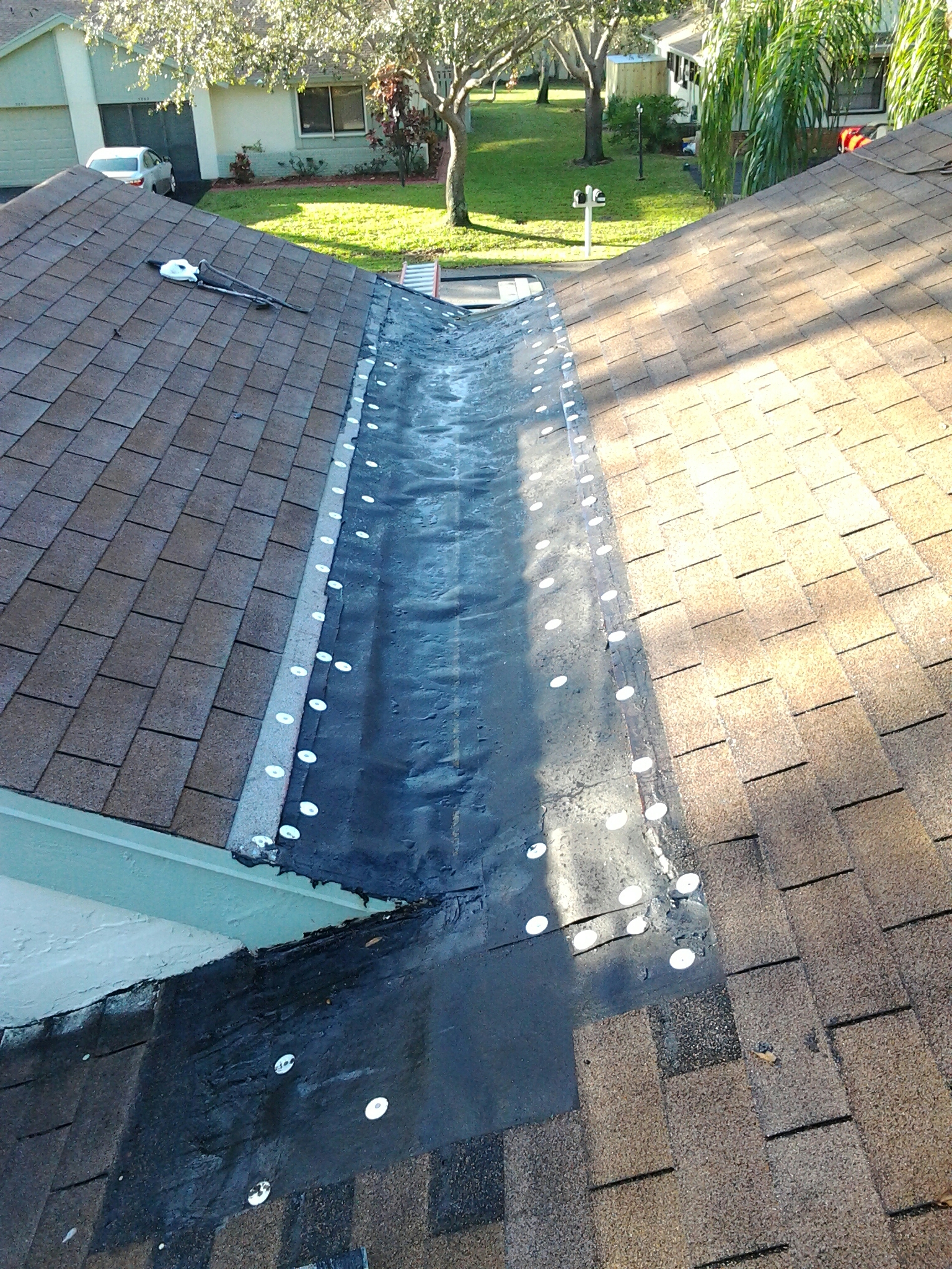 Delray Beach, FL - Mike and Earl Johnston roofing ready to install new metal in cricket.