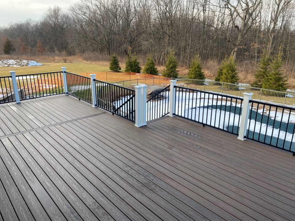 Howell, MI - This upper level Trex deck over looking the homeowners pool will be a great hang spot come summer time! This deck features spiced rum decking with a vintage lantern border! For this deck we used black Trex Signature railing with white post sleeves, and white post caps with solar lights! We're building all winter long.