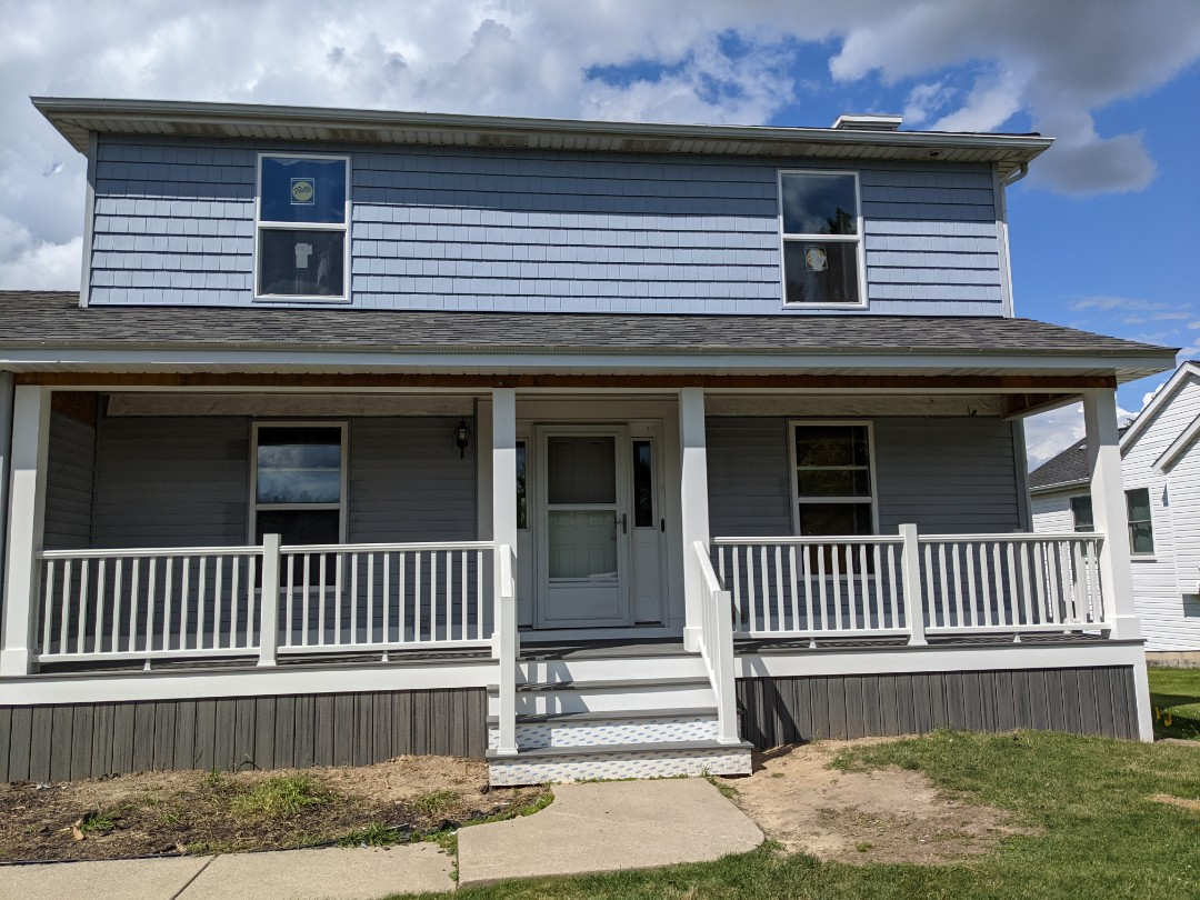 Howell, MI - A beautiful covered porch with Trex decking and trex rail with new windows and shake siding in Howell
