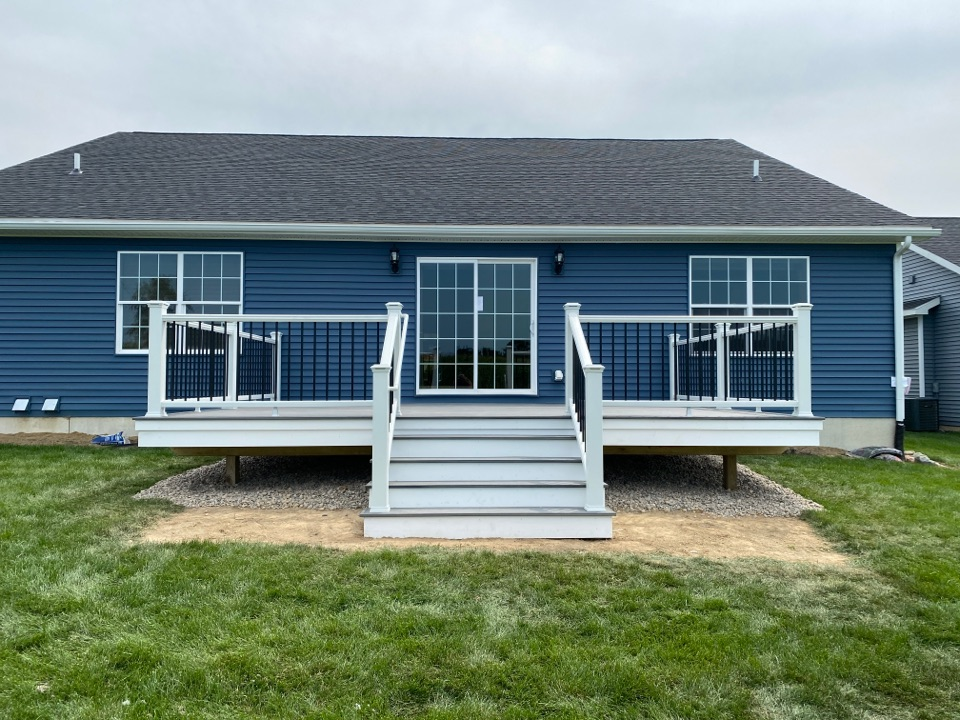 Just finished up this lovely 14x20 Trex deck. This deck features Island Mist Decking, white Trex Transcend rails with black spindles, and lighted Trex post caps. All finished up in Fowlerville.