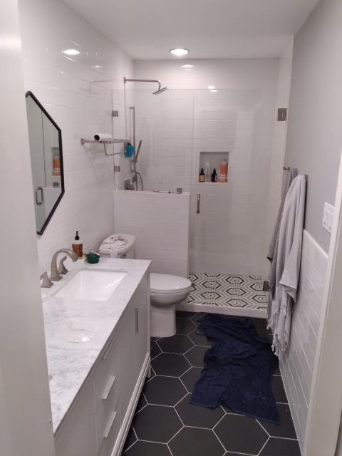 Cedar Park, TX - There was a wall between the toilet and the vanity with a pocket door, then another wall between the toilet and the shower. We removed all that, plus floors and remodeled bath with new tile on floors and walls, glass doors for the shower, and barn door to enter the bathroom.