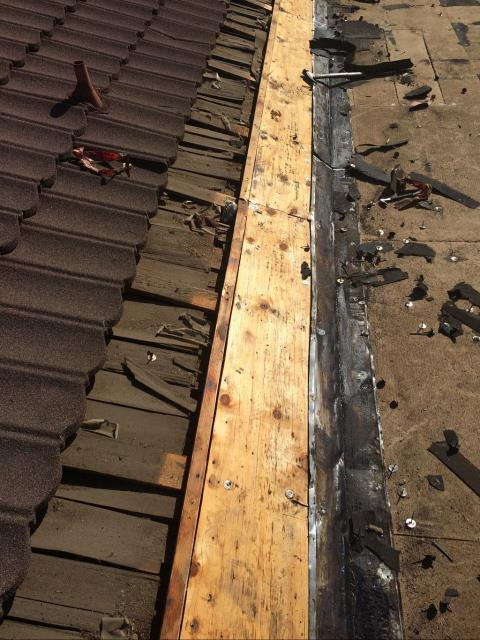 Orange, CA - We needed to remove 3 courses of metal roofing to tie in the new roof system. We made sure to seal it under the wood shake and re install the metal roofing.