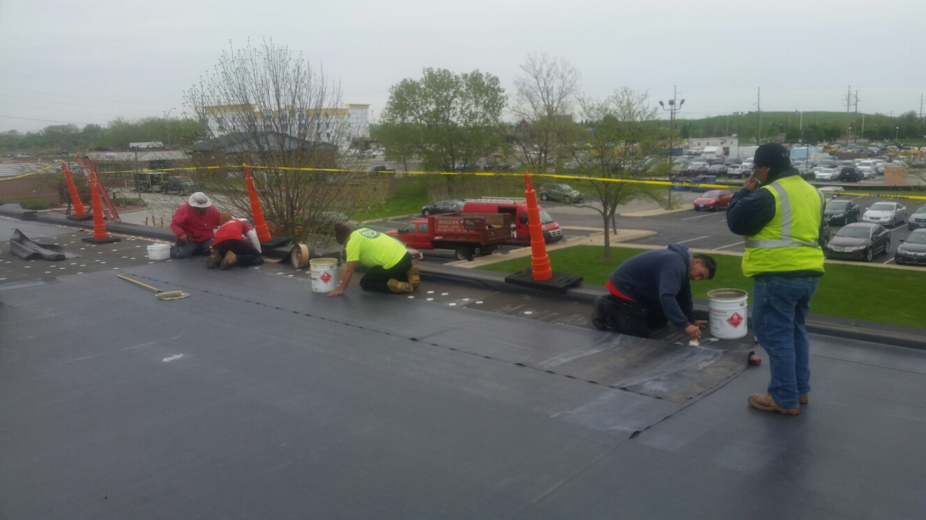 Munster, IN - Applying adhesive for installation of EPDM fully adhered  roofing system.
