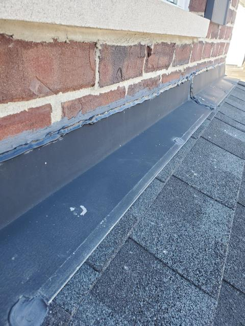 Elgin, IL - Our roofing installer removed the existing caulk from along the entire front of the building and installed all new caulk along the roof to wall flashing.