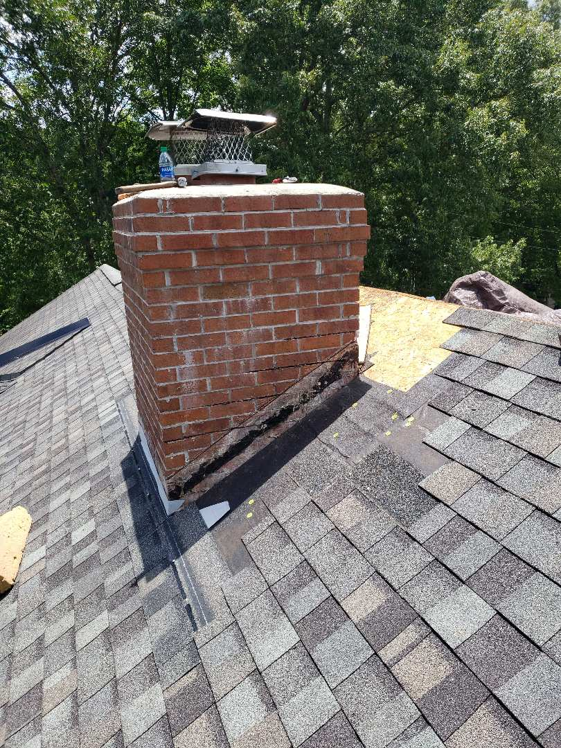 Knoxville, TN - Mobley Brothers repaired a chimney with a severe leak on this traditional brick home. Tamko Heritage Thunderstorm Grey shingles, roof flashing, a new ridge vent and GAF StormGuard were installed on a elegant brick home.