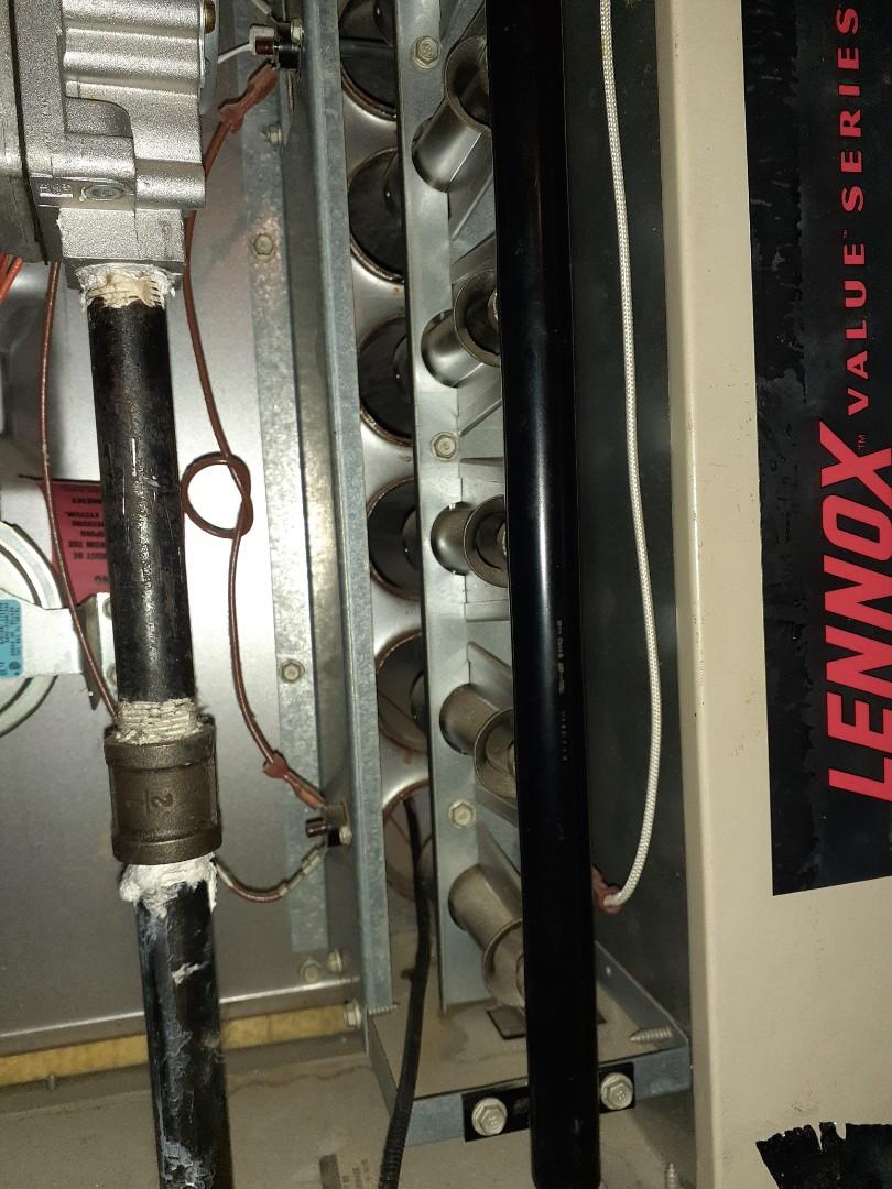 Inspecting a heat exchanger inside a Lennox furnace for cracks