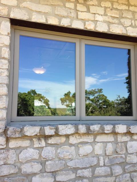 Boerne, TX - Renewal by Andersen awning windows in Boerne, TX. Sandtone frame in stone exterior.
