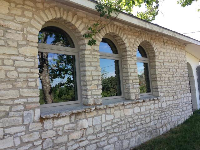 Boerne, TX - Boerne home with circle top windows over operating windows installed by Renewal by Andersen. Sandtone frame set in stone exterior.