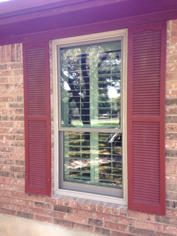Boerne, TX - Sandtone Andersen double hung window in brick with custom colored shutters