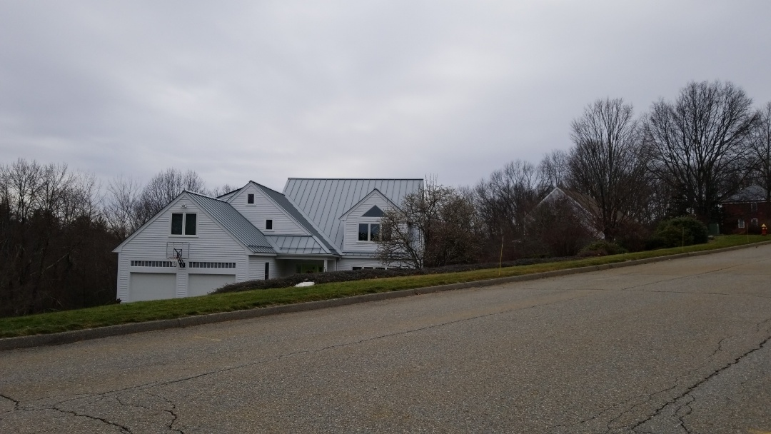 Hudson, MA - Standing seam aluminium lifetime roof in dove gray. This was the right solution for a house that was once covered in ice dams all winter