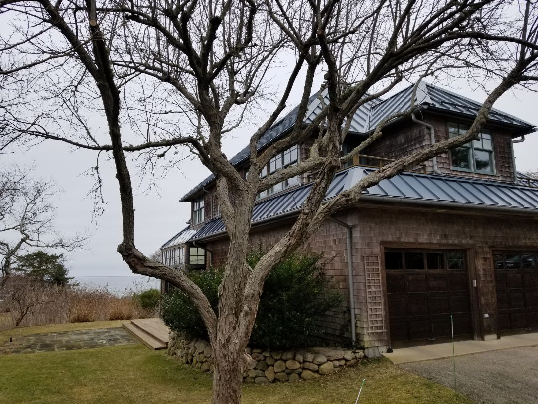 Falmouth, MA - Gray standing seam aluminum roof on ocean front home. Hip roof classic.