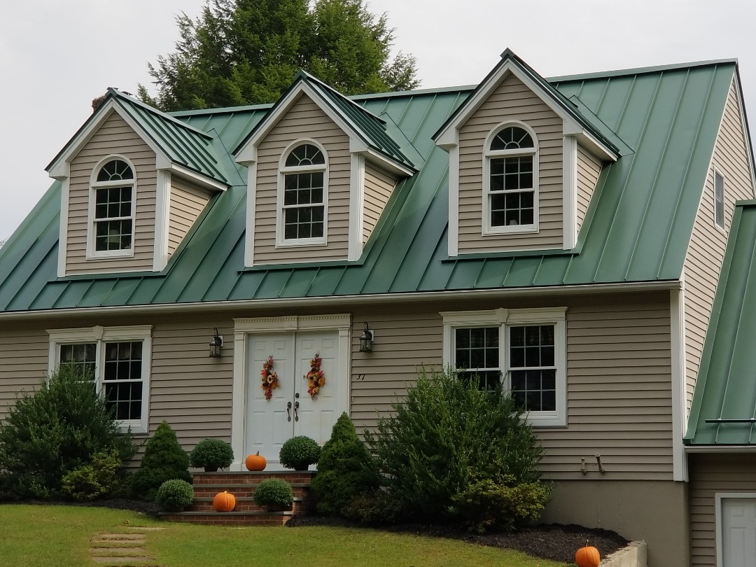 Dudley, MA - Beautiful cape style home with attached garage. Standing seam aluminum metal roof in forest green.