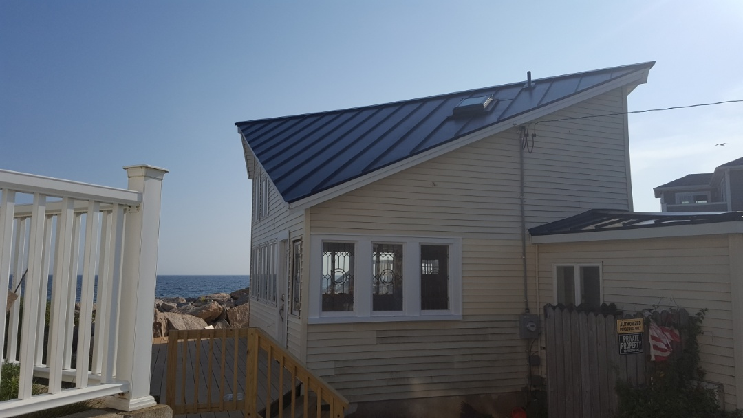 Westerly, RI - Just completed this cottage makeover, on the way to become a beach front year round home. This new aluminum standing seam roof will handle about anything that comes its way hurricane rated in the color subnet blue.