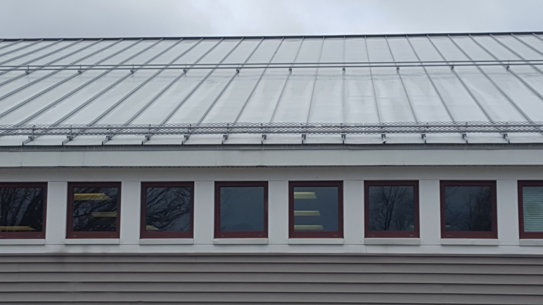 Spencer, MA - The proper amount of snow retention on this commercial building's standing seam metal roof. Needed to protect pedestrians walking along the sidewalk.