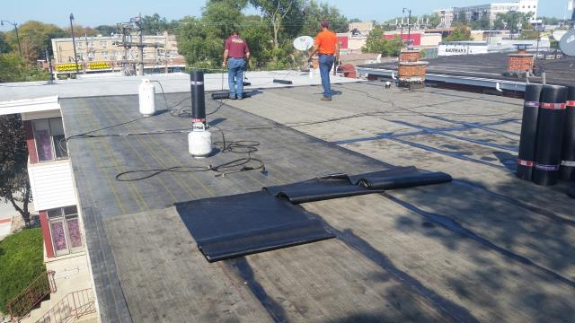 Flat roof in progress using a modified bitumen roofing system.