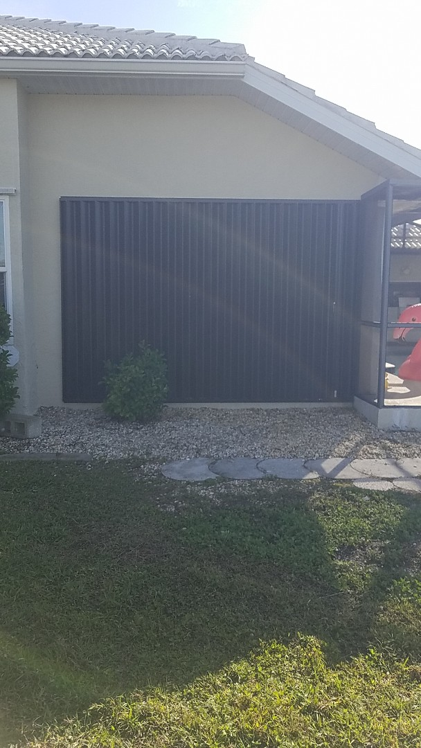 Installed bronze accordion hurricane shutter