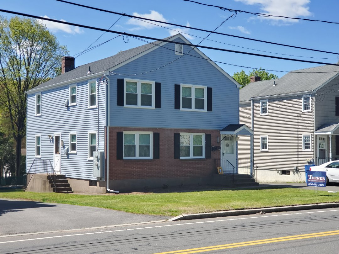 Manchester, CT - New GAF Timberline shingles in the color Charcoal, New Certainteed Mainstreet vinyl siding in the Color Oxford Blue with Black Raised Panel Shutters, New Sunrise vinyl replacement windows.