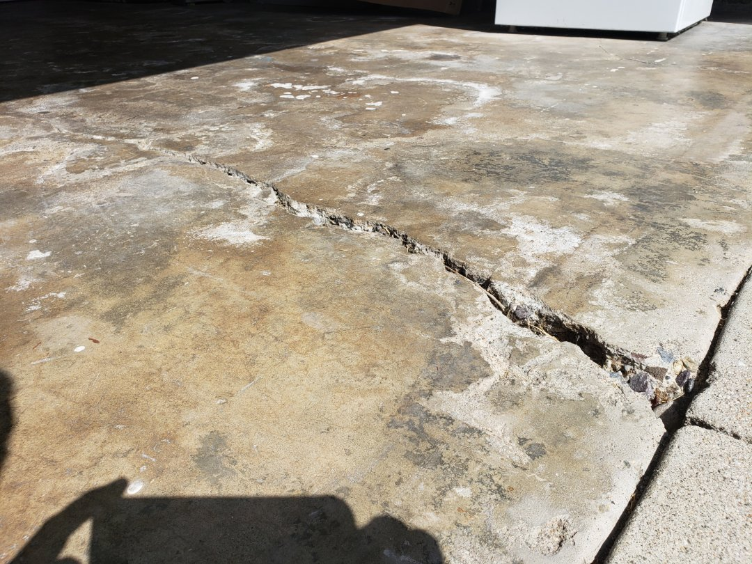 Huntington Beach, CA - 1966 home with a garage floor without rebar and vapor barrier. Slab is cracked and water intrusion surfacing through slab beneath.