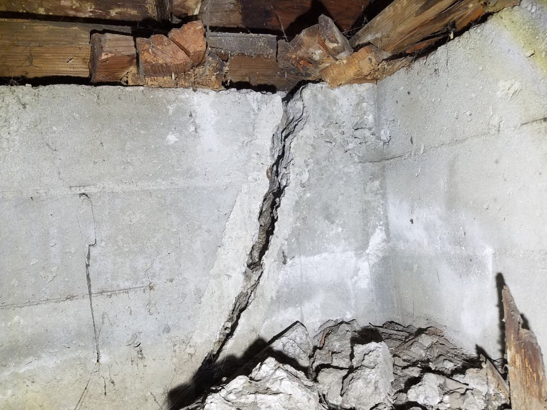 "Foundation crack with shimmed sill plate. Settlement down a total of amost 7""."