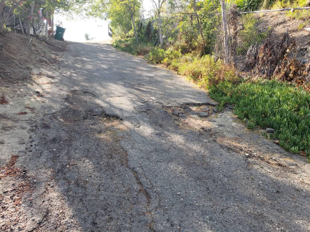 Santa Ana, CA - Ground settlement undermining asphalt driveway