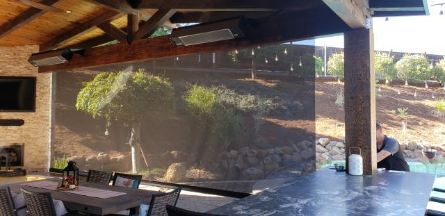 """Livermore, CA - Large Sentry Screen from Sunesta, Installed in Livermore, Awning Pros Inc. This screen is 20' 7"""" wide x 10' drop, a unique installation where the screen needed to be large, facing the western sun, but had obstacles like the built in bar table on one side and the stone wall and long bench seat on the other side. This prevented a way to guide the screen up & down.  The fabric was an 8% openness from Soltis, Serge Ferrari."""