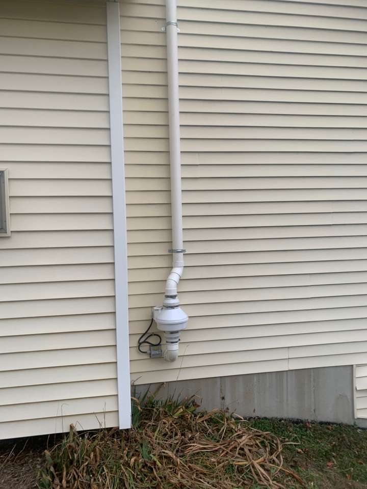 Rockford, MI - Here's a picture of an exterior radon mitigation system we installed behind the chimney of this house to hide the system from view.