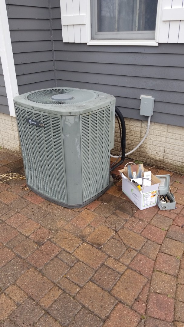 Performing maintenance and replacing the contactor, capacitor, condenser fan, and service disconnect after troubleshooting compressor issues on a 2003 Trane A/C in rural Boone.