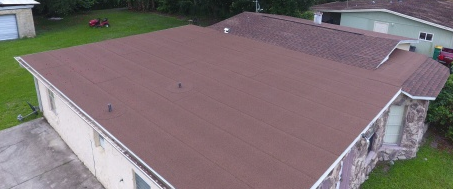 Kissimmee, FL - Replacing the worn-out asphalt shingles on a roof that has both a flat and an angled portion with GAF Timberline® HD® Shingles with StainGuard Protection in a Hickory color. The crew is also installing a GAF StormGuard FilmSurfaced Leak Barrier to protect the client from future leaks.