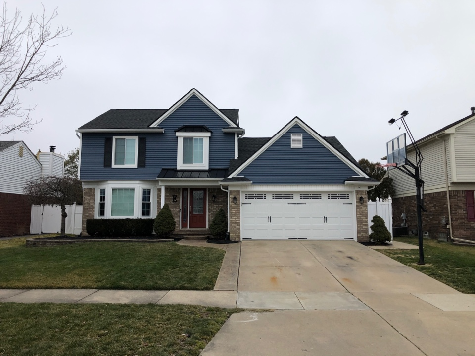 Brownstown Charter Township, MI - Full exterior overhaul. Roof replacement GAF HDZ charcoal. New siding and trim / color-Newport bay. New windows with pro via and a new metal roof