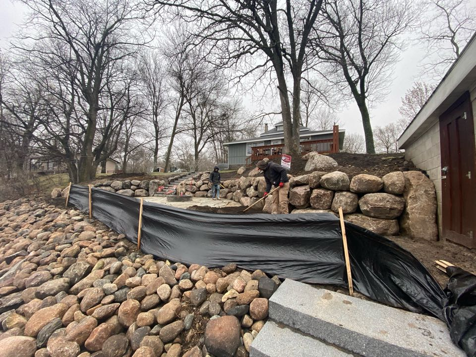 Litchfield, MN - Boulder walls, granite steps, flagstone, planting beds, boulder outcroppers and a wood fire pit finishing install on Lake Minnie-Belle. Plants to be installed later this spring.