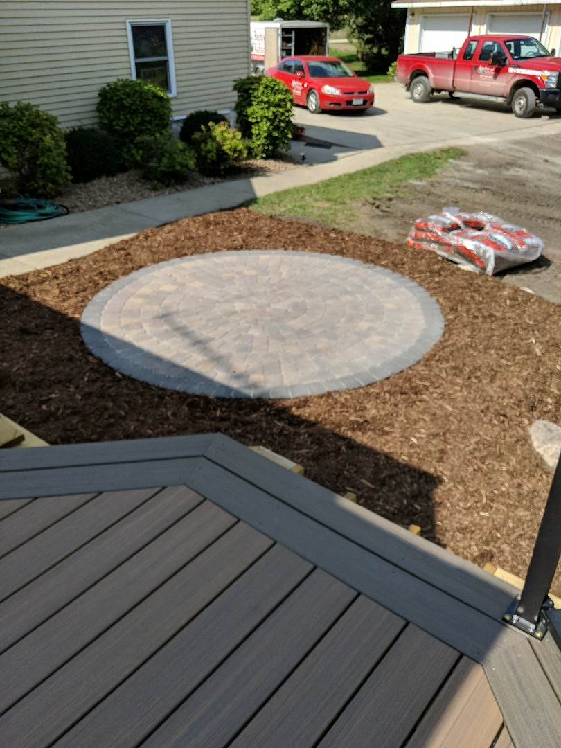 Howard Lake, MN - small cute cobble paver patio in a mulch bed coming off the deck.