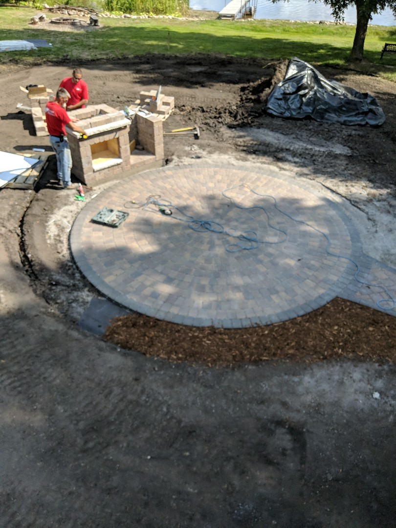 Howard Lake, MN - A larger cobble paver patio with a brand new cobble fireplace with a hearth and a wood box.