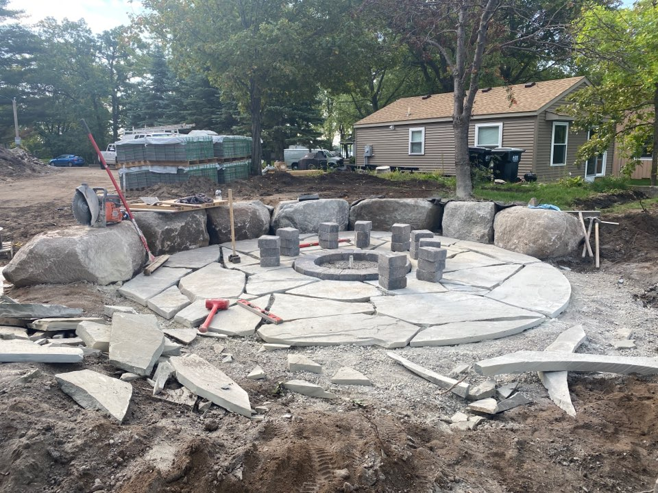 Big Lake, MN - Flagstone firepit with seat boulders being installed on lake Mitchell in big lake