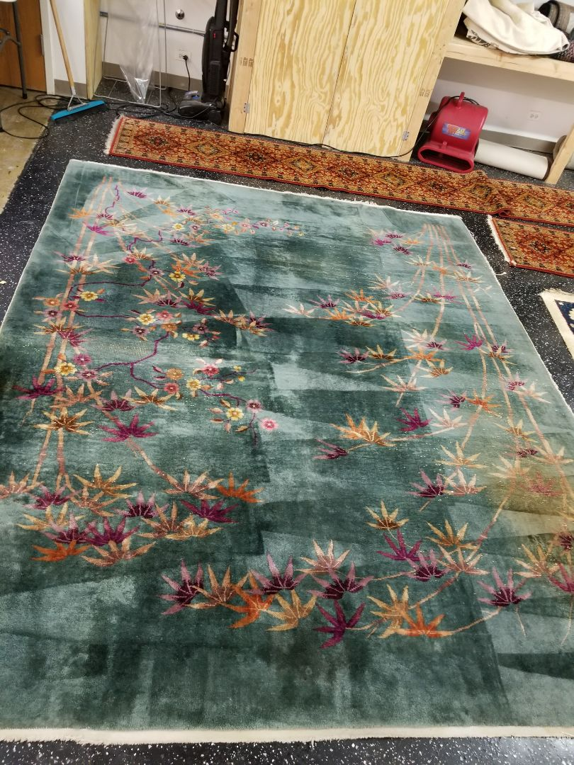 Teal wool rug with delicate flower embroidery across the rug, cleaned and treated by technician Jerry for pet odor and general dirt. Area rug was picked up out of the Chicago area.
